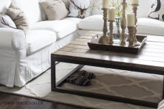 white-slipcovered-sectional-oversize-clock-board-and-batten-wall-chandelier-large-coffee-table