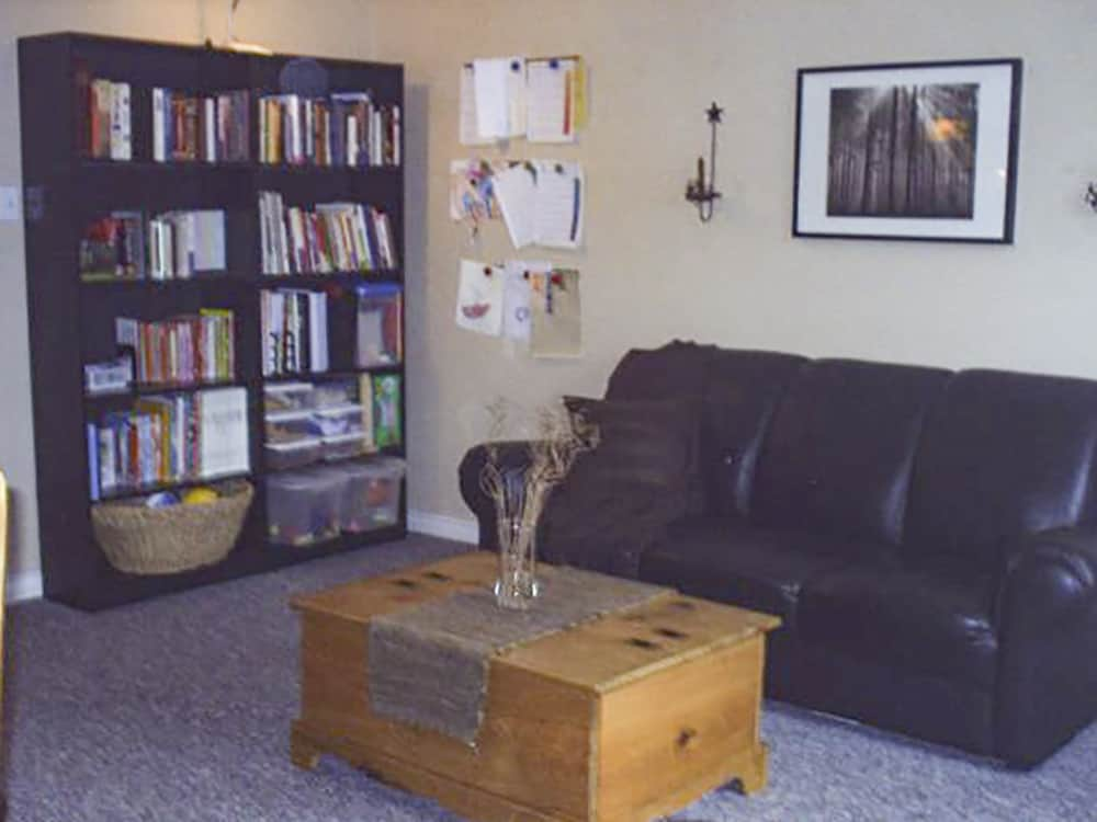 living room with black leather couch, organized shelves