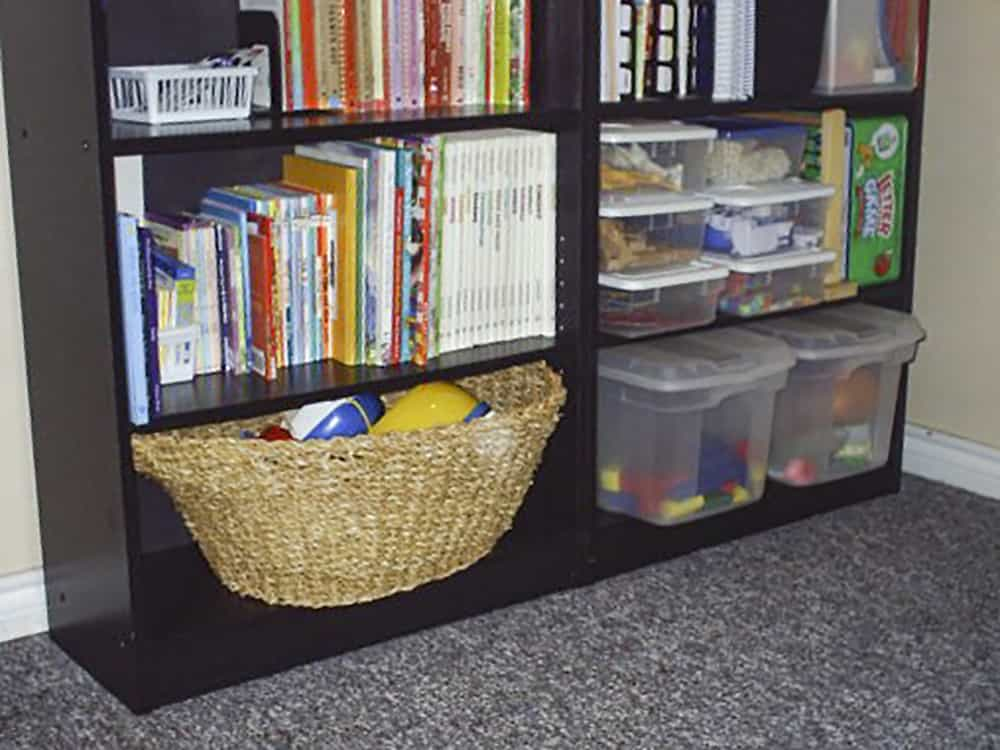 lower shelves on black bookcase, with bins of toys and baskets for organizing kids toys