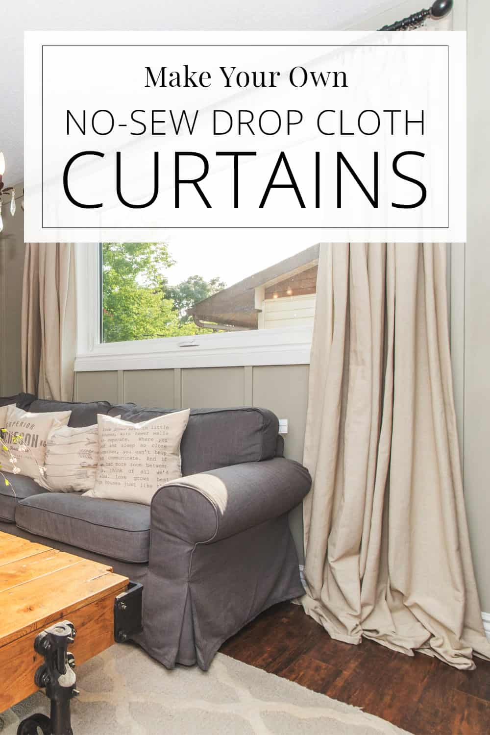 drop cloth curtains on living room window, grey sectional couch, chandelier