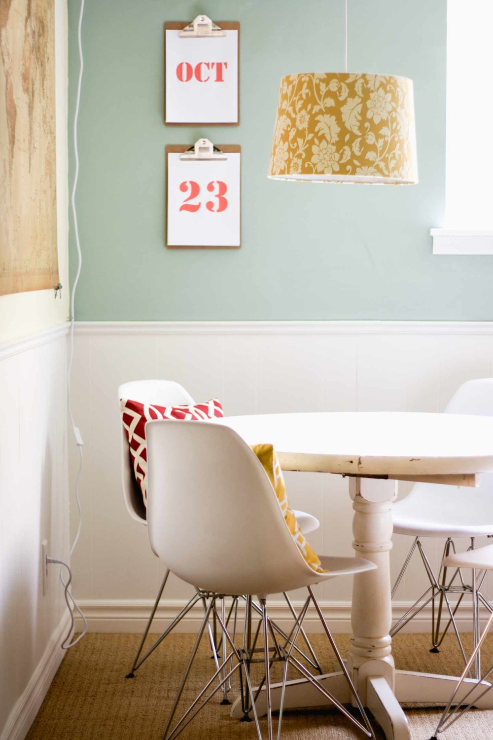 white pedestal table, white eames chairs, hanging pendant light in yellow and clipboard perpetual calendar