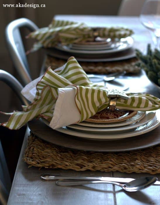 christmas table setting white plates rattan placemats green stripe napkins