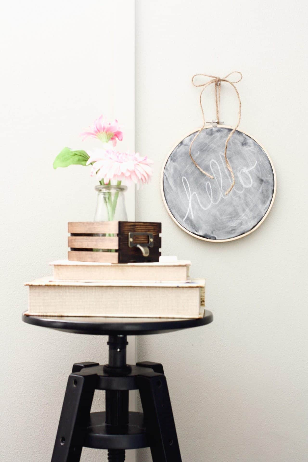 stack of books on a stool, mini crate with pink flower, embroidery hoop chalkboard hanging on wall behind