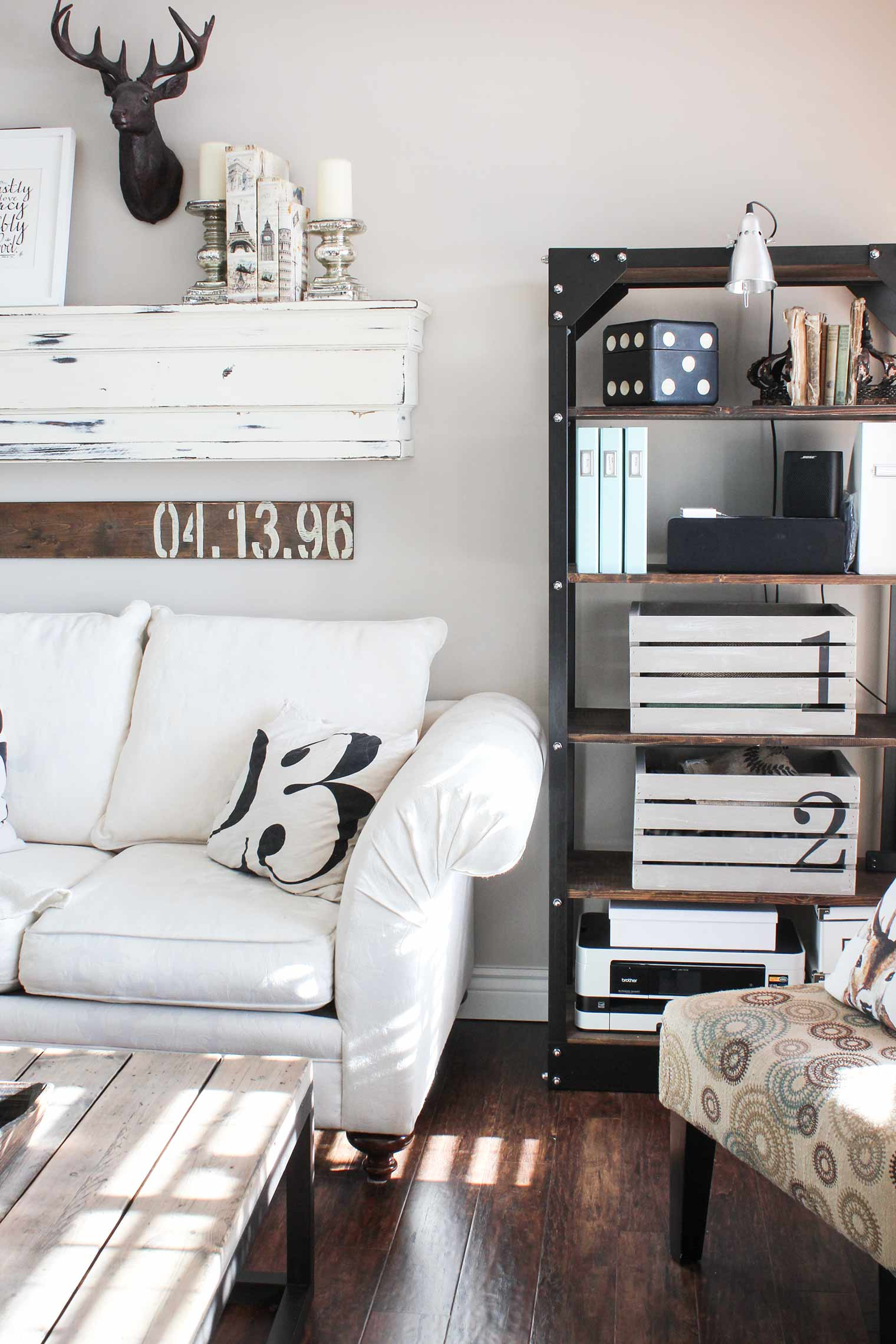 crates on shelves, white sofa, black and white 23 pillow, special date stenciled sign