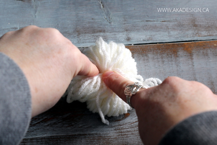 tie a knot around pom poms