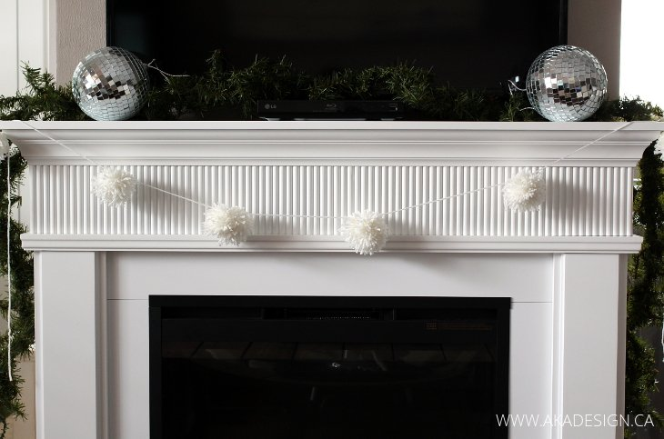 white fireplace with pom pom garland