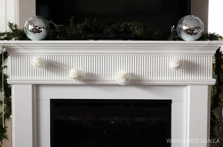 white fireplace with pom pom garland