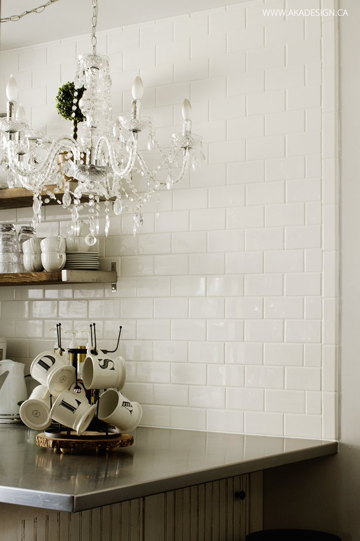 Subway tile, crystal chandelier, stainless counter, open shelving