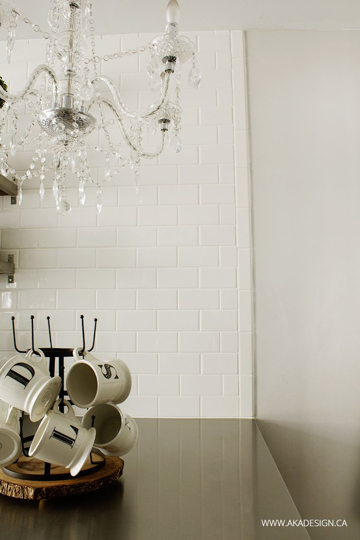 White Subway Tile Wall, Stainless Counter, Crystal Chandelier