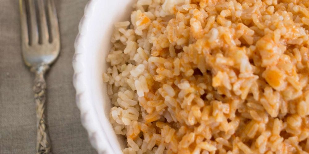 rice with sauce in white bowl with antique fork