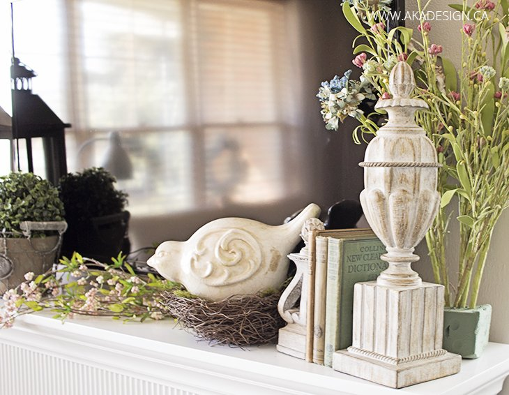 white electric fireplace mantel with spring decor like lanterns, greenery and ceramic birds