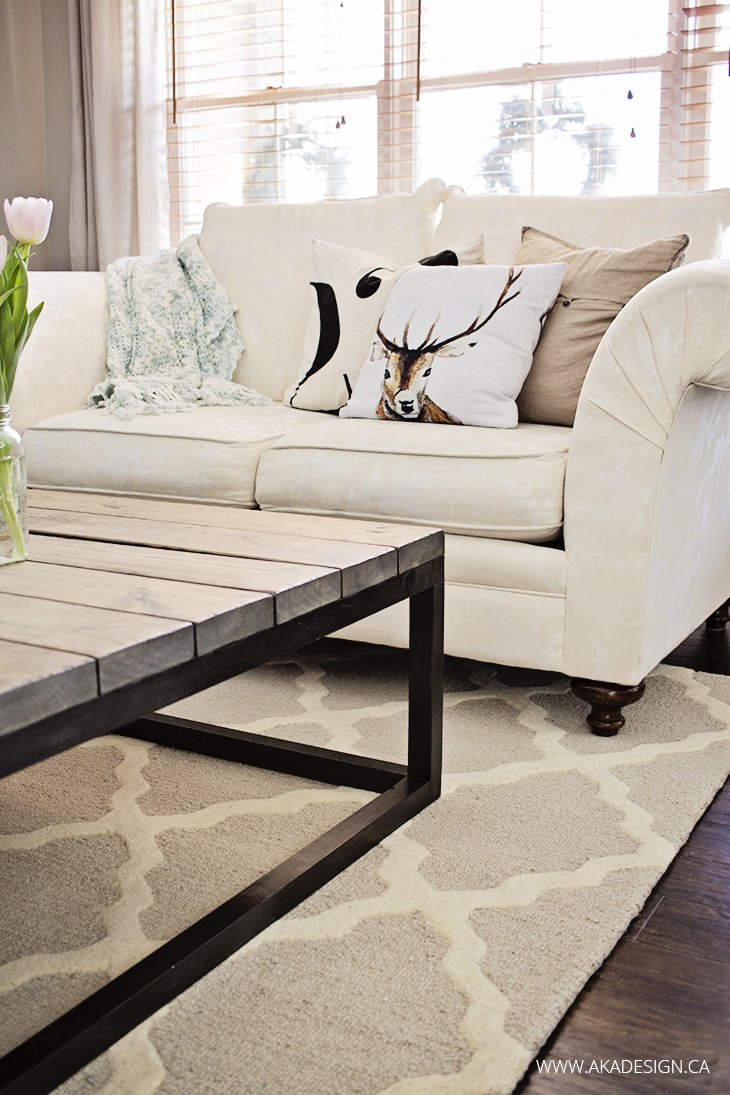 white living room couch dark wood floor trellis rug