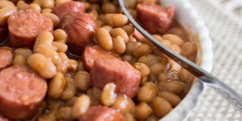 wieners and beans in a white bowl, spoon