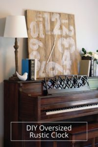 Oversized Rustic Clock propped on a piano with a white lamp