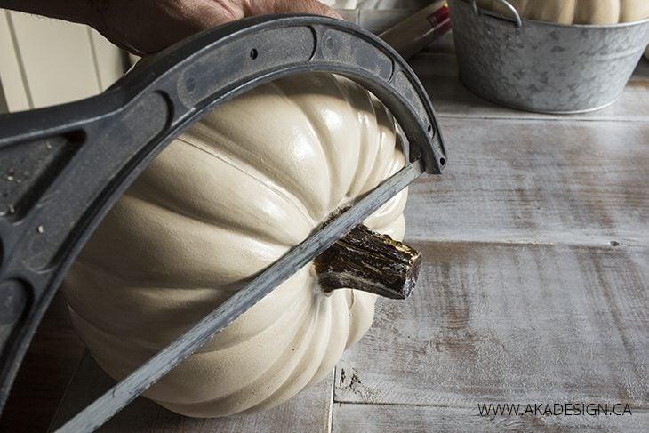 cutting off pumpkin stem with hacksaw