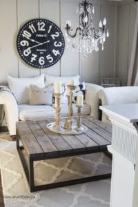 white living room with chandelier and trellis rug
