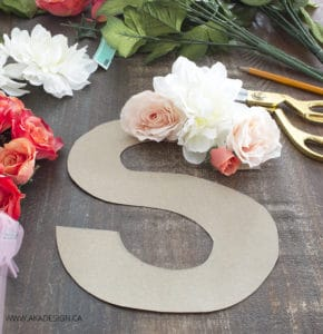 Hot glue faux flowers to cardboard for monogram