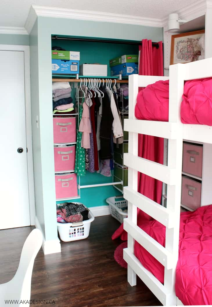 pink and aqua girls bedroom with open closet and cloth buckets as storage