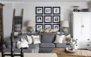 grey sectional, urn lamps, blanket ladder, armoire, black and white family photo grid wall