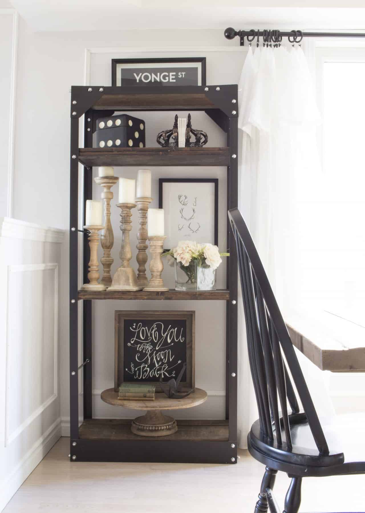 rustic industrial metal and wood shelves in dining room filled with farmhouse style decor like candle sticks and antlers