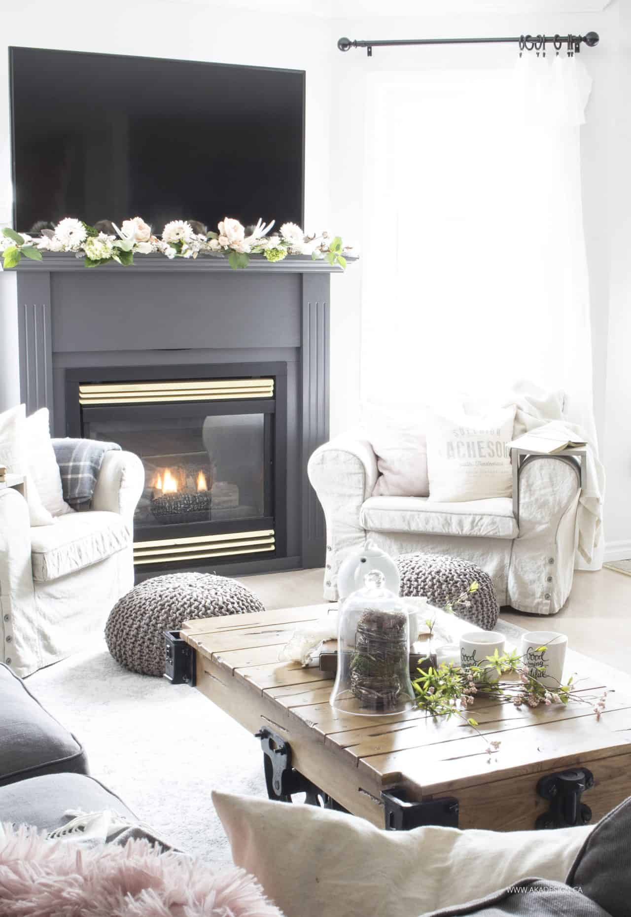 grey painted fireplace mantel with spring flowers flanked by two arm chairs