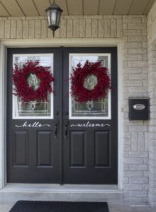 black front doors red berry wreath