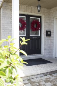 black front double doors with red berry wreaths