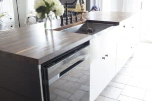 black stainless dishwasher | black island | white cabinets | stainless farmhouse apron front sink