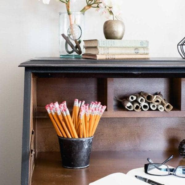 secretary desk painted black, pencils, flowers