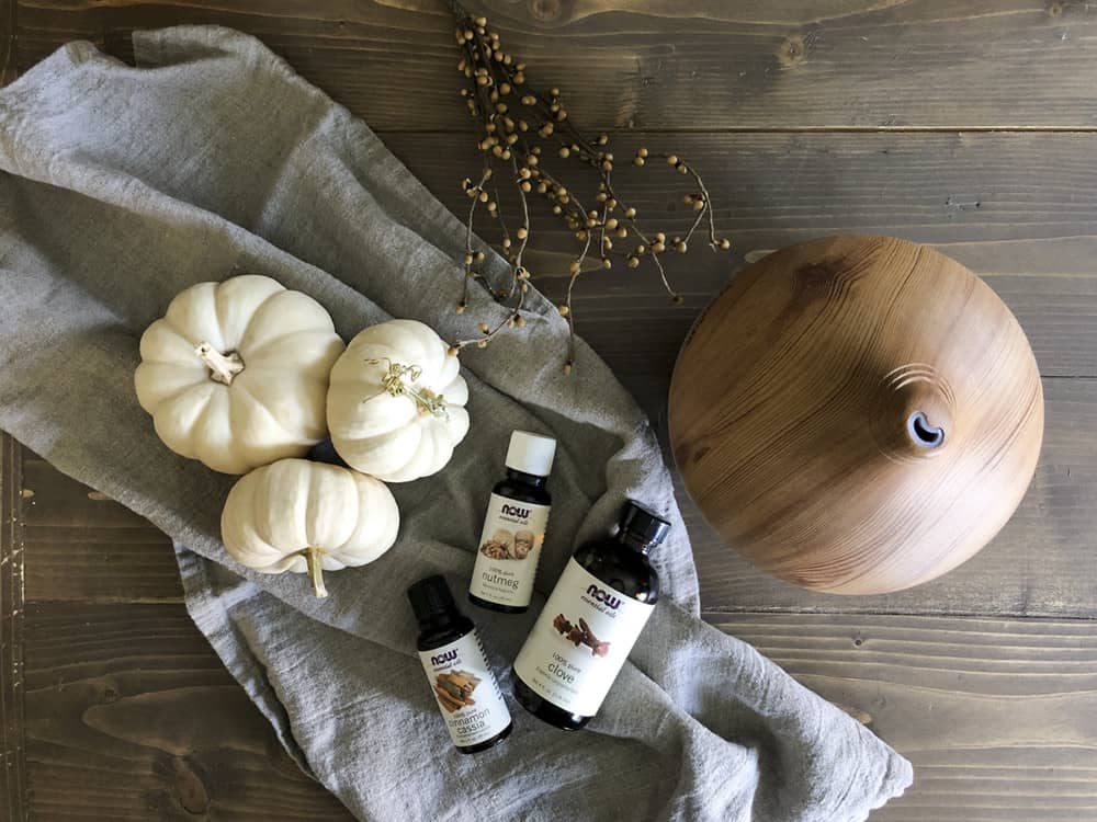 fall essential oil blends bottles on table with diffuser beside