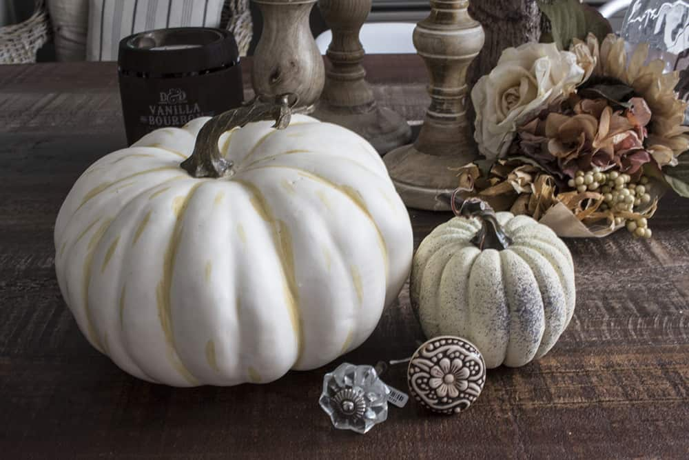 fake pumpkins and cabinet knobs on rustic table