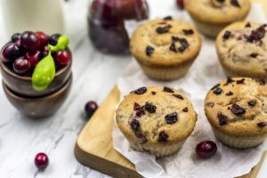 muffins with cranberries on a wooden board