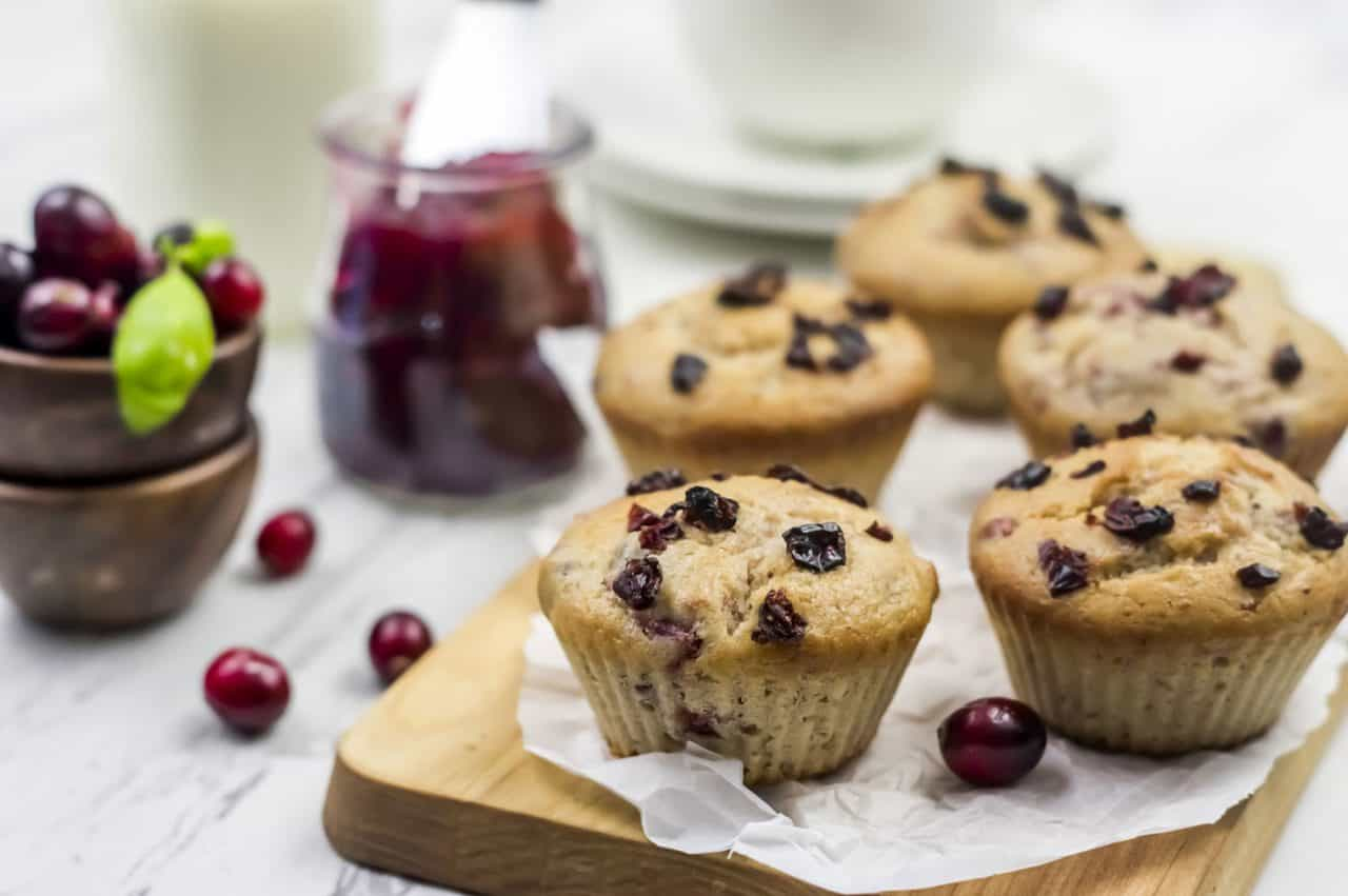 cranberry muffins on wood cutting board