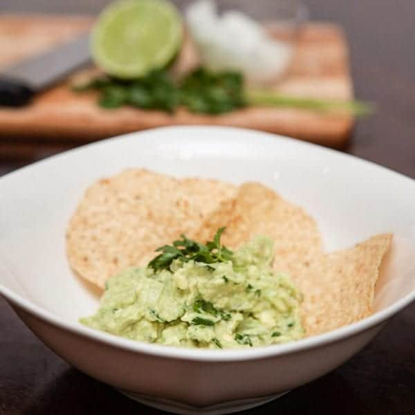 guacamole in a white bowl with round corn chips
