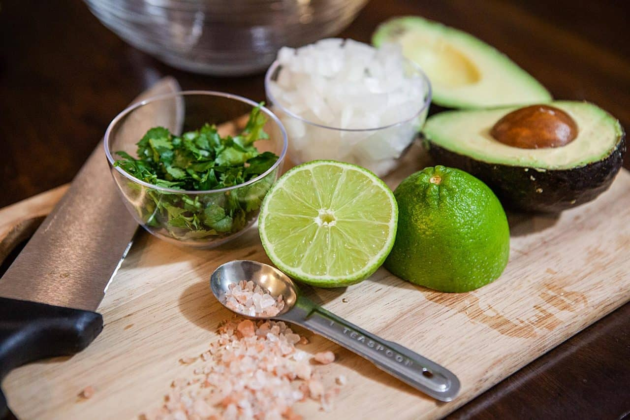 lime, onions, avocado on cutting board for making guacamole