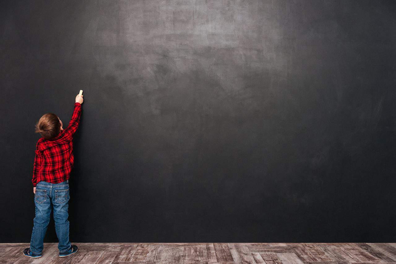 boy at chalkboard, plaid shirt