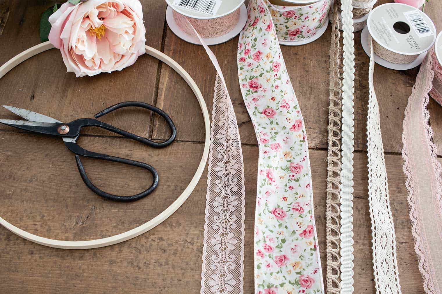 blush pink ribbons on table ready to cut with vintage black scissors