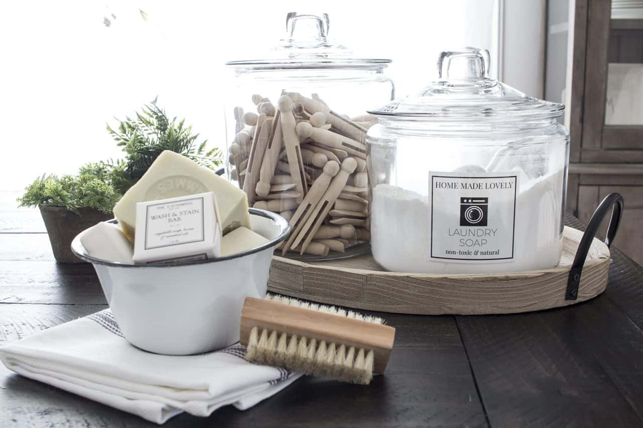 glass jars with lids holding homemade laundry soap and wooden clothespins showing printable cleaner labels in use
