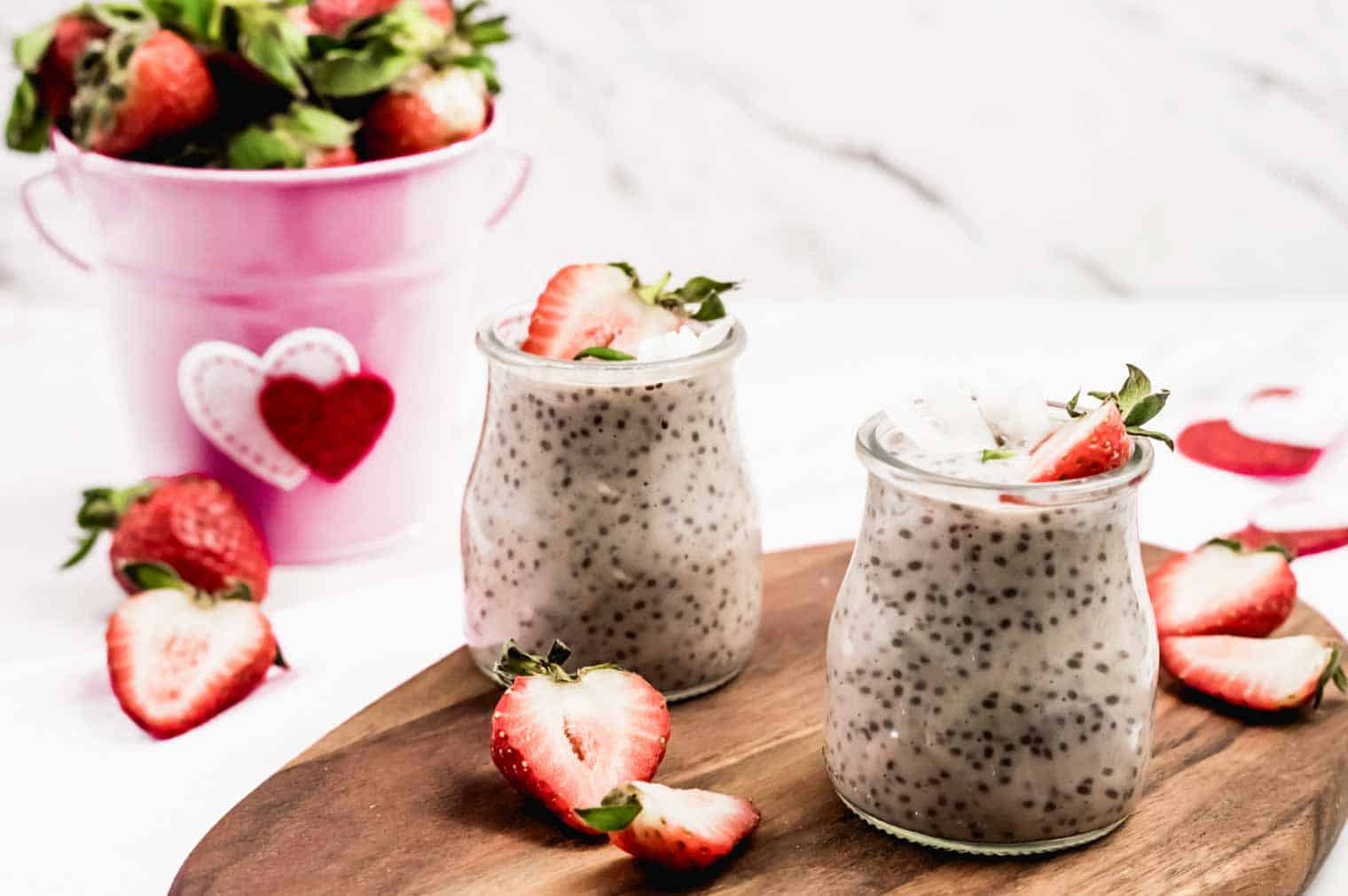 strawberry chia seed pudding in two jars, on cutting board with cut strawberries around