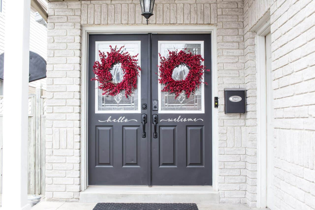 black double front doors with black door hardware and red berry wreaths