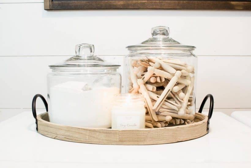 powdered laundry soap in a large jar with scoop beside a larger jar filled with old fashioned clothes pins