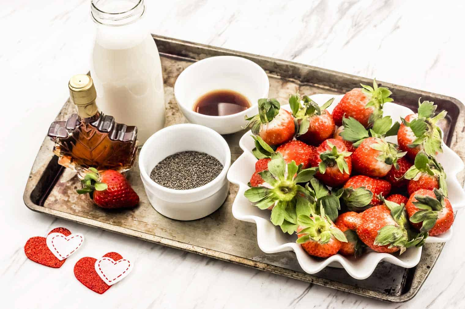milk, chia seeds, maple syrups and strawberries in dishes on a tray, to make chia seed pudding