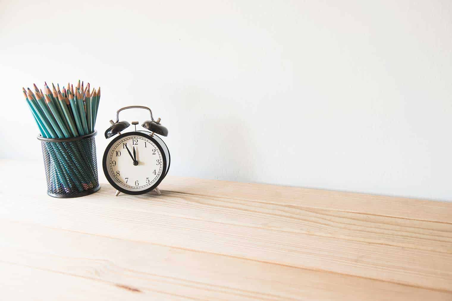 turquoise pencils in a wire holder beside an alarm clock on a desk top