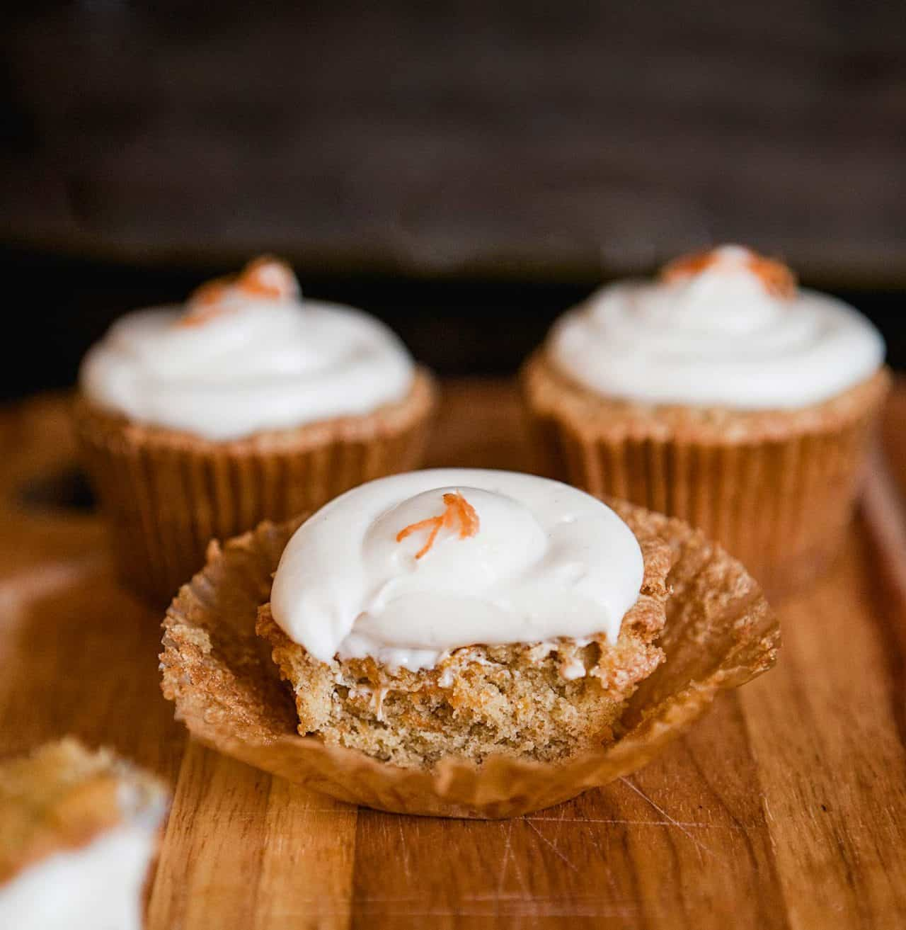 bite out of one carrot cupcake with cream cheese frosting