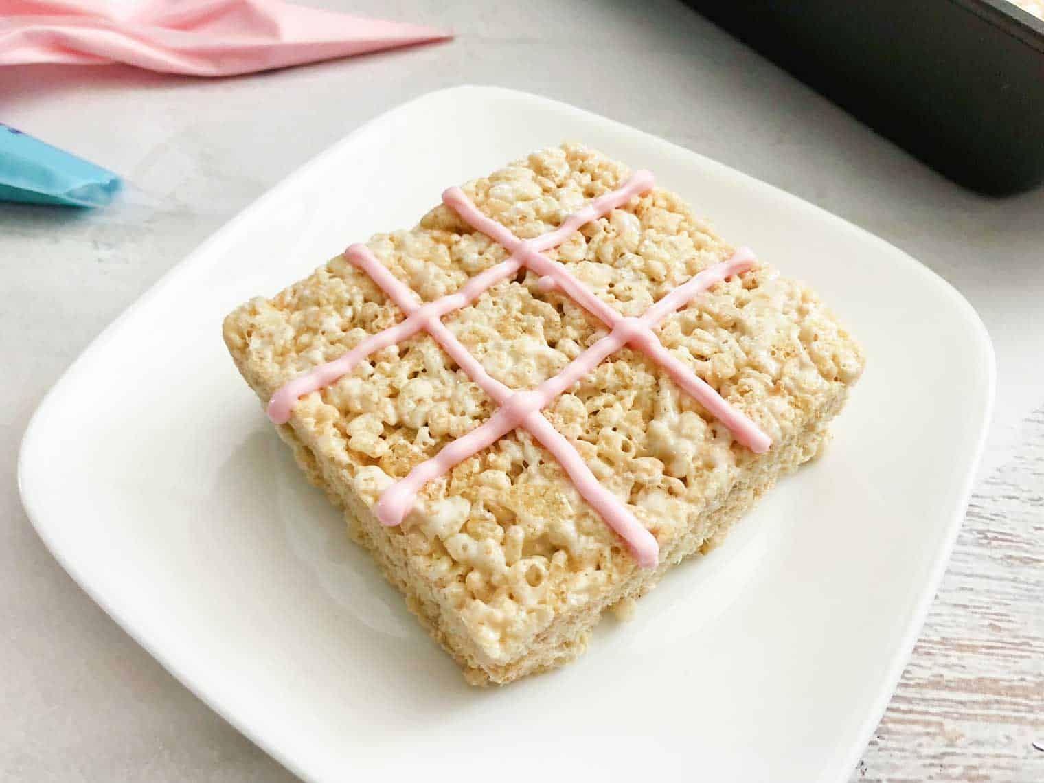 make tic tac toe board with icing on each rice krispie square