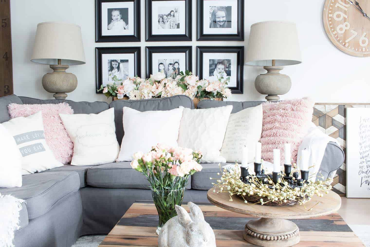 grey sectional, black framed photos on gallery wall, spring flowers in living room