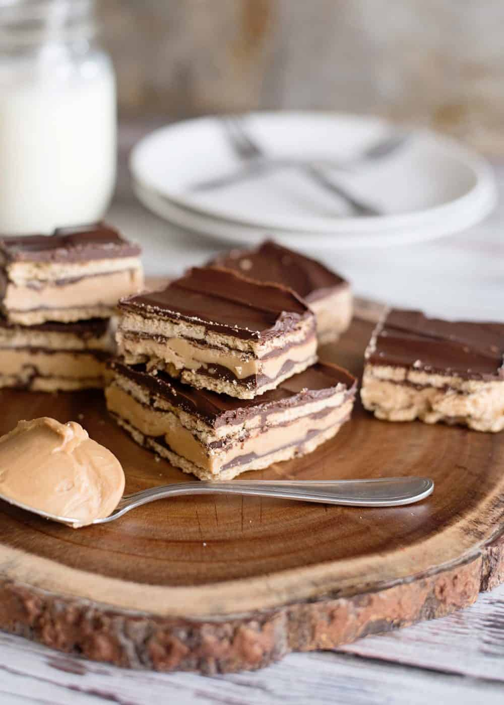 no-bake peanut butter patty bars on log slice with glass of milk in background