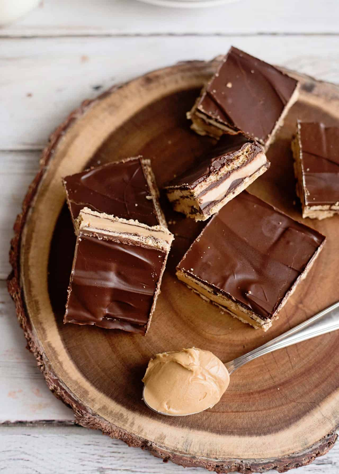no-bake peanut butter patty bars on log slice with scoop of peanut butter