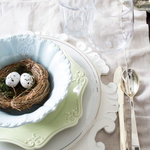 pastel spring table setting with antique gold rimmed plates, spring green plates and aqua bowls
