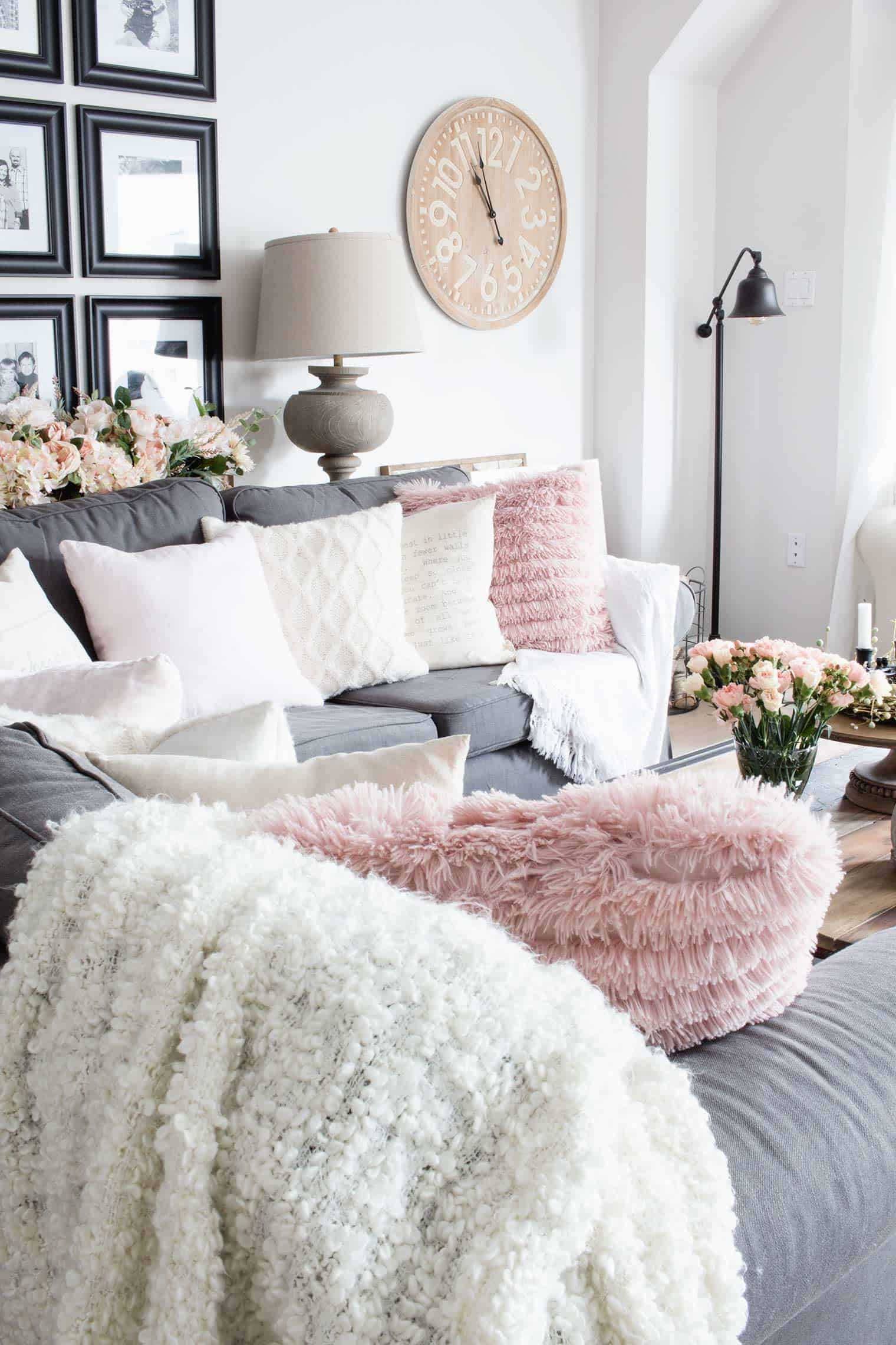 blush and cream throw pillow-filled grey sectional in living room